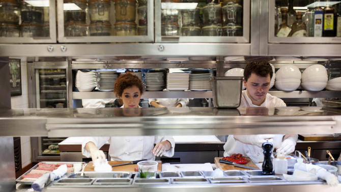 In this Tuesday Aug. 28, 2012 photo, staff at CharlieTrotter's restaurant in Chicago are seen preparing for dinner. U.S. service companies grew at a faster pace in August than July and stepped up hiring, further evidence that the economy may be improving. (AP Photo/Sitthixay Ditthavong)