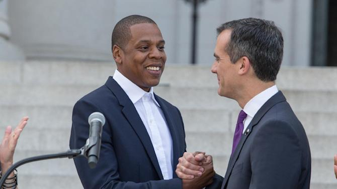 Jay-Z, also known as Shawn Carter, left and Mayor Eric Garcetti clasp hands as they announce the Made in America Festival from the steps of City Hall on April 16, 2014 in Los Angeles. (Photo by Paul A. Hebert/Invision/AP)