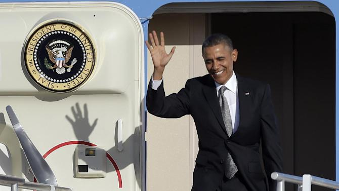 President Barack Obama waves as he arrives at Miami International Airport, Friday, Nov. 8, 2013, in Miami. President Obama will be participating in fund raising events during his visit to Miami. (AP Photo/Alan Diaz)