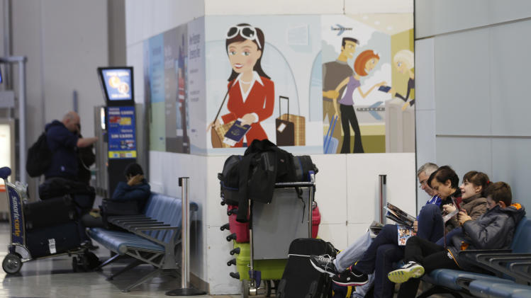 People sit near their luggage at Newark Liberty International Airport, Thursday, Dec. 27, 2012 in Newark, N.J. An overnight storm caused some delays at the airport. (AP Photo/Julio Cortez)
