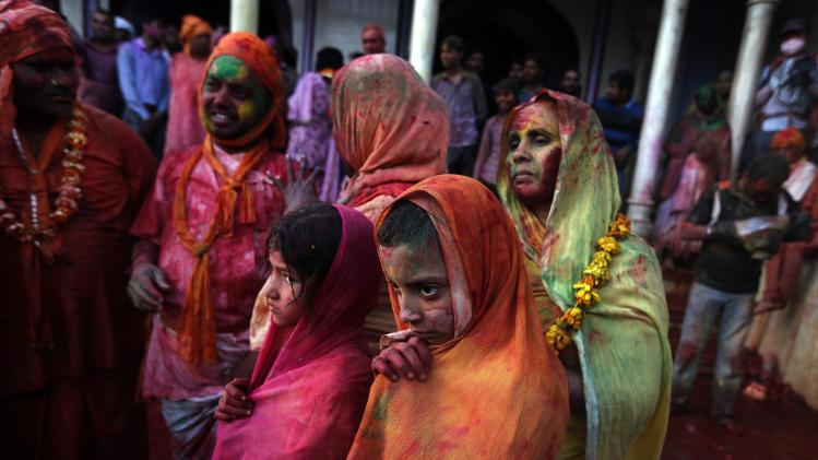 "Girls covered with coloured powder and water shiver from cold as they stand inside a temple during ""Lathmar Holi"" at Nandgaon village in the northern Indian state of Uttar Pradesh"