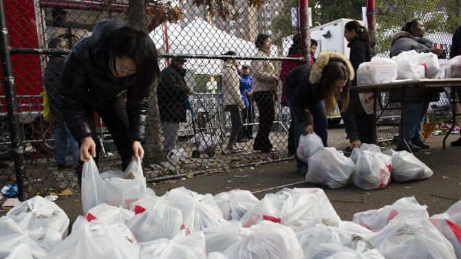 A queue of people forms behind a fence as they wait for distribution of food, water, and other supplies intended for residents of the Lower East Side who remain without power due to Superstorm Sandy, Friday, Nov. 2, 2012, in New York. In Manhattan, where 226,000 buildings, homes and business remain without power, Consolidated Edison says they should have service restored by Saturday.  (AP Photo/ John Minchillo)