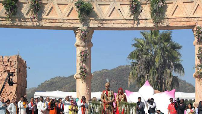 """In this photo supplied by The New Age newspaper of South Africa and taken Thursday May 2, 2013, guests watch as the bridal couple, Vega Gupta, centre right, and Aakash Jahajgarhia, are pulled across a pool on a float at Sun City's Palace of the Lost City, South Africa, during their wedding ceremony. The self-proclaimed """"wedding of the century"""" has become a public relations disaster for the government since a private jet appears to have received diplomatic courtesies, allegedly bypassing customs procedures, when the jet landed the wedding party at the military Waterkloof Air Force Base near Pretoria, South Africa.  The jet landed Tuesday angering many South Africans who see the scandal as a case of cronyism linking big business and government and igniting accusations that security laws were breached. (AP Photo/The New Age)"""