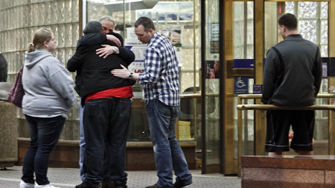 People hug outside the emergency room at Thomas Jefferson Hospital in Philadelphia, Saturday, April 6, 2013, after fireman Capt. Michael Goodwin was brought to the hospital. A fire caused a partial roof collapse that killed Goodwin and injured a colleague who was trying to rescue him, officials said. (AP Photo/ Joseph Kaczmarek)