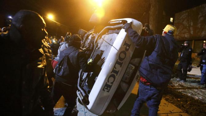 Protesters try to flip over a Ferguson police car, in Ferguson