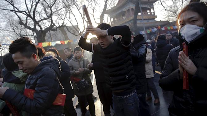 People burn incense and pray for good fortune on the first day of the Lunar New Year of the Monkey at Yonghegong Lama Temple in Beijing