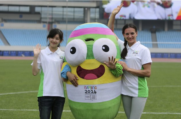 Russia's pole-vaulting athlete Isinbayeva waves as she poses for photographs with the mascot of the Nanjing 2014 Youth Olympic Games in Nanjing