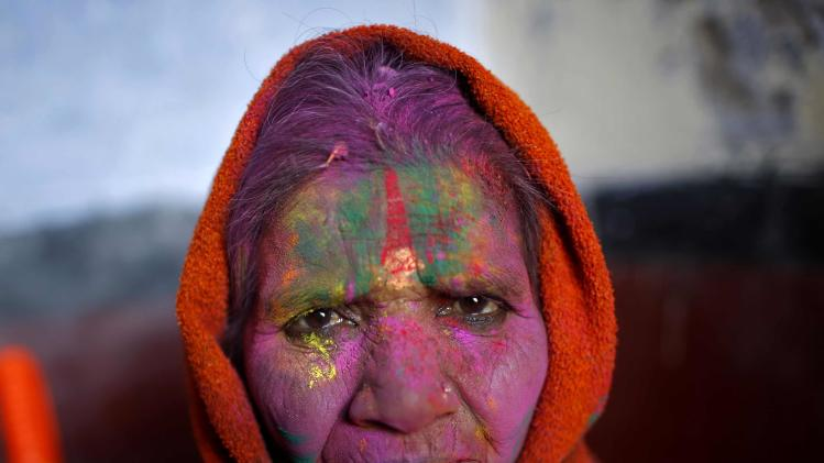 A widow with her face smeared with coloured powder watches the Holi celebrations in Vrindavan