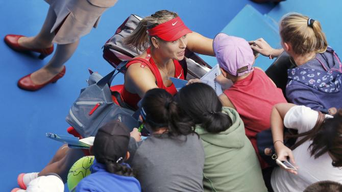 Sharapova of Russia signs autographs after defeating Peng of China to win their women's singles match at the Australian Open 2015 tennis tournament in Melbourne