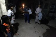 Children watch on as &quot;mousaherati&quot; beat their drums in the streets of Baghdad&#39;s Sadr City to wake the sleeping for the &quot;suhoor&quot;, the meal that precedes a Muslim&#39;s daily fast during the holy month of Ramadan