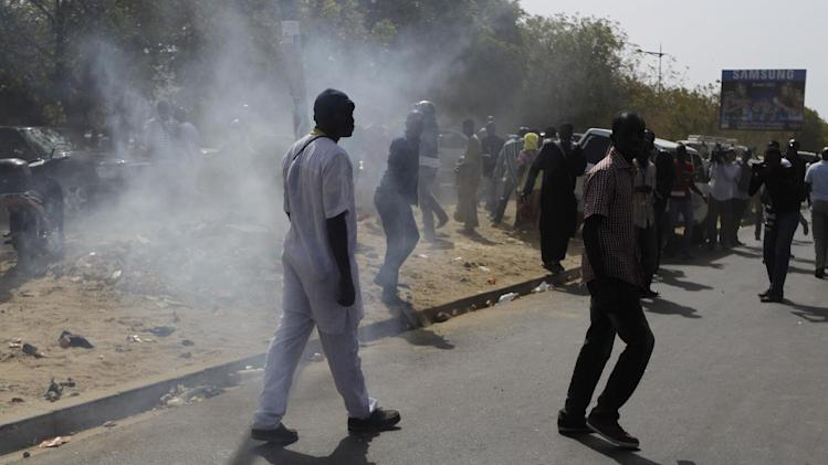 People walk past tear gas, fired by security forces to disperse a group of supporters of President Abdoulaye Wade, outside the polling station where Wade was due to vote in the Point E neighborhood of Dakar, Senegal Sunday, March 25, 2012. Senegalese voters are deciding Sunday whether to give their 85-year-old president another term in office, or instead back his one-time protege Macky Sall in a runoff election that could oust the incumbent of 12 years. (AP Photo/Rebecca Blackwell)