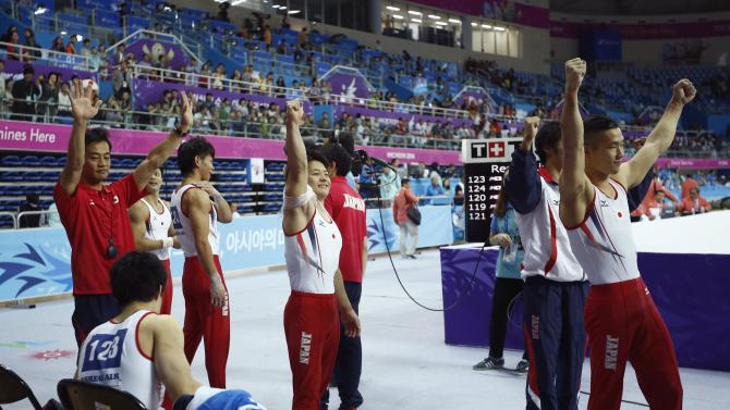 Members of Japan's men's gymnastics team react upon hearing they won the gold medal for the team gymnastic competition during the 17th Asian Games in Incheon