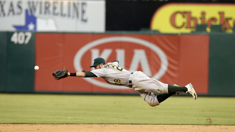 Oakland Athletics second baseman Eric Sogard stretches out on an attempt to reach a ball hit by Texas Rangers' Alex Rios that went for a single in the fifth inning of a baseball game, Sunday, July 27, 2014, in Arlington, Texas. (AP Photo/Tony Gutierrez)
