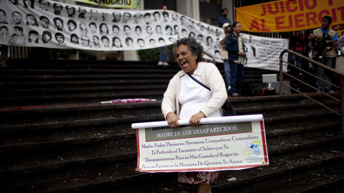 A woman celebrates outside the court at the end of a trial in Guatemala City, Tuesday, Aug. 2, 2011. The court sentenced three former special forces soldiers to 6,060 years in prison each for the massacre of more than 200 men, women and children, one of hundreds that occurred during Guatemala's 36-year civil war, which ended in 1996. Some 240,000 people, mostly Mayan Indians, vanished or died. (AP Photo/Rodrigo Abd)