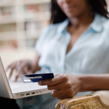 Woman-using-credit-card-and-mac-laptop_web