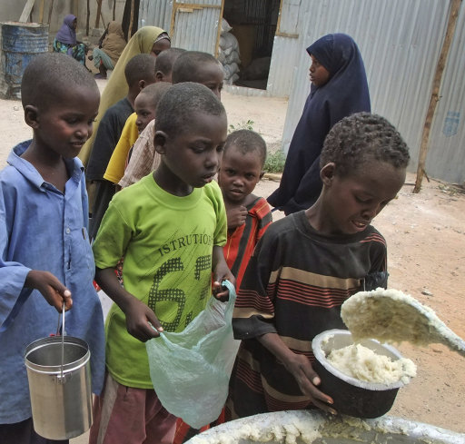 Somali children from southern Somalia are given cooked food at a distribution center in Mogadishu, Somalia, Thursday, Aug. 25, 2011. The United Nations says famine will probably spread to all of southern Somalia within a month and force tens of thousands more people to flee into the capital of Mogadishu. (AP Photo/Farah Abdi Warsameh)