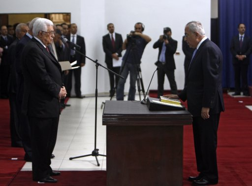 Palestinian President Abbas stands in front of Prime Minister Fayyad as he is being sworn-in in Ramallah