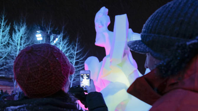 IMAGE DISTRIBUTED FOR BRECKENRIDGE RESORT CHAMBER- A couple uses a Smart iPhone to snap a photograph of the Team Catalonia, Spain, 'Banyista Nua' (Homage To Picasso) at the outdoor gallery at the Riverwalk Center during the 23 annual International Snow Sculpture Championships in Breckenridge, Colo., on Saturday, Jan. 26, 2013. Each sculpture started out of a 12 foot tall, 20-ton block of compacted snow at the outdoor art gallery. The sculptures will remain on display through Feb. 3, 2013. Visit www.gobreck.com for more information. (Nathan Bilow / AP Images for the Breckenridge Resort Chamber)