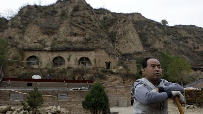 In this photo taken Thursday, Oct. 18, 2012, a peasant pauses from working near cave dwellings that characterize the region where Chinese Vice President Xi Jinping used to live during his youth when he was sent to learn peasant virtues at Liangjiahe village in northwestern China's Shaanxi province. Xi, 59 and the country's vice president is expected to take over as head of the ruling party in November, 2012, before becoming president in 2013 of an increasingly assertive China. The Liangjiahe years are among scant details known about Xi's life and personality partly because he himself chronicled them as a key formative experience. (AP Photo/Ng Han Guan)