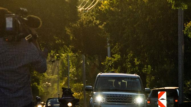 Olympic athlete Oscar Pistorius, silhoetted in front vehicle, center, arrives at a relatives home in Pretoria, South Africa, Friday, Feb 22, 2013. Pistorius was released on bail and will return to court June, 4, 2013 to face a charge of pre-meditated murder in the shooting deth of his girlfriend Reeva Steenkamp. (AP Photo/Waldo Swiegers)