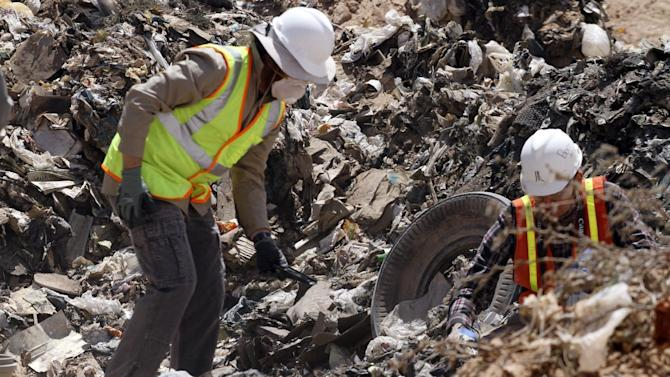 FILE - In this April 26, 2014 file photo, workers sift through trash in search for decades-old Atari 'E.T. the Extra-Terrestrial' game cartridges in Alamogordo, N.M.   A cache of Atari game cartridges dug up in an Alamogordo landfill last year has generated more than $100,000 in sales.  An estimated 850 games that sold on eBay over the last several months in 2015 brought in close to $108,000.  (AP Photo/Juan Carlos Llorca, File)