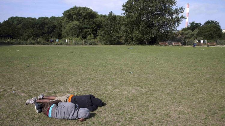 "Two African migrants sleep on the grass in the ""jungle"" close to a chemical factory in Calais"