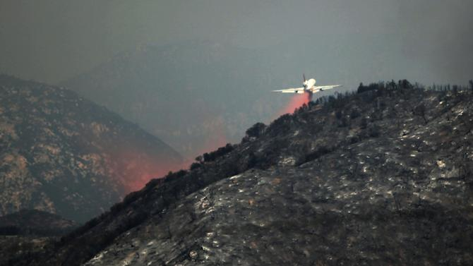 A DC-10 tanker drops fire retardant on a ridge line at the Angeles National Forest in California, Tuesday, Sept. 4, 2012. It could be a week before firefighters can contain this 3,600-acre blaze because of high temperatures and rugged terrain in thick brush that hasn't burned in a couple of decades. (AP Photo/Damian Dovarganes)