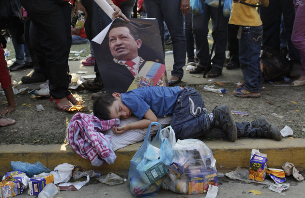 A woman holds a poster of Venezuela's late President Hugo Chavez over a sleeping boy as she stands in line to see Chavez's body lying in state at the military academy in Caracas, Venezuela, Friday, Ma