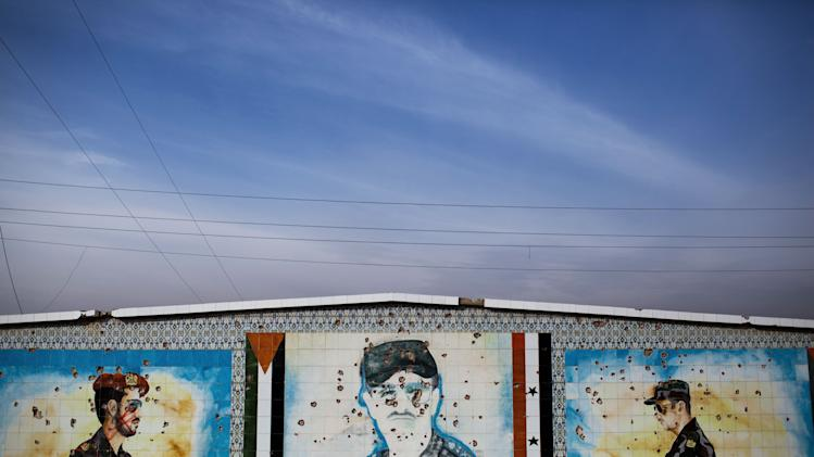 A mosaic of Hafez Al Assad is seen after being shot at by FSA soldiers after heavy clashes with government forces at a military academy besieged by the rebels in Tal Sheer, Syria, Sunday, Dec 16, 2012 (AP Photo / Manu Brabo)