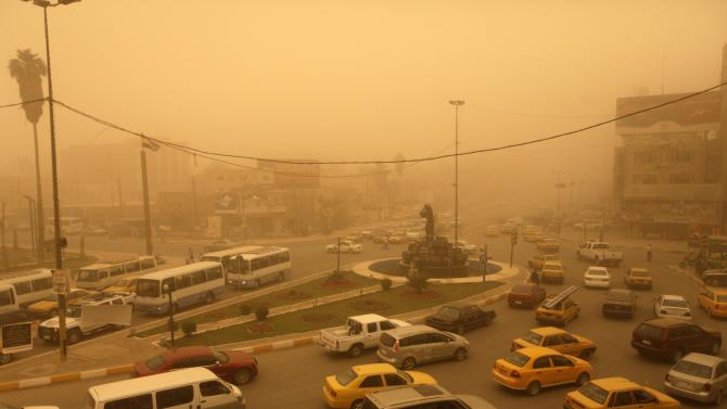 Traffic snakes through Kahramana Square during a heavy sandstorm in Baghdad, Iraq, Tuesday, May 22, 2012. The sandstorm prompted the shutdown of Baghdad's airport on Monday and brought travel complications for envoys trying to reach the Iraqi capital for nuclear talks between Iran and six world powers scheduled to begin Wednesday.(AP Photo/ Khalid Mohammed)