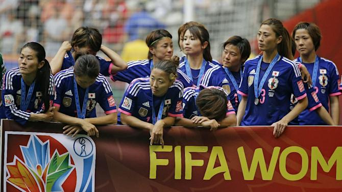 Players on Japan's Women's National Team react during post-match ceremonies after the United States beat Japan 5-2 in the FIFA Women's World Cup soccer championship in Vancouver, British Columbia, Canada, Sunday, July 5, 2015. (AP Photo/Elaine Thompson)
