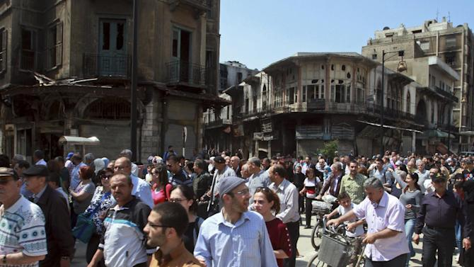 Residents return to the al-Hamidiyeh neighborhood of Homs, Syria, Saturday, May 10, 2014. Thousands of Syrians streamed into war-battered parts of the central city of Homs for the first time in nearly two years Saturday, many making plans to move back just days after rebels surrendered their strongholds to pro-government forces. The surrender deal is widely seen as a victory for Assad weeks ahead of a presidential election on June 3 that he is expected to win, giving him a mandate to continue his violent crackdown on rebels in the Syrian civil war, which activists say has killed more than 150,000 people. (AP Photo)