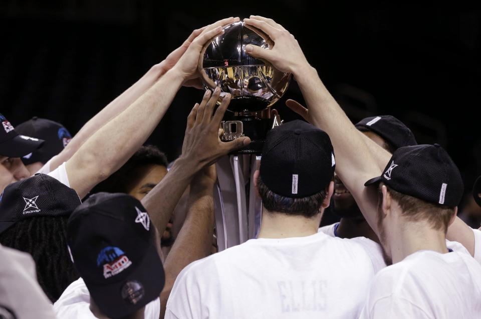 Saint Louis teammates put their hands on the Atlantic 10 championship trophy after an NCAA college basketball game  for the championships of the Atlantic 10 Conference tournament  Sunday  March 17, 2013, in New York. Saint Louis beat Virginia Commonwealth 62-56.  (AP Photo/Seth Wenig)