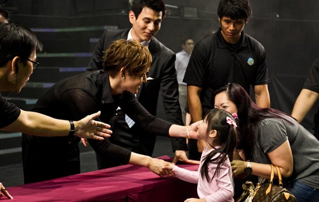 Kim touches the face of a young fan during the high five-session. (Photo courtesy of Running Into The Sun)