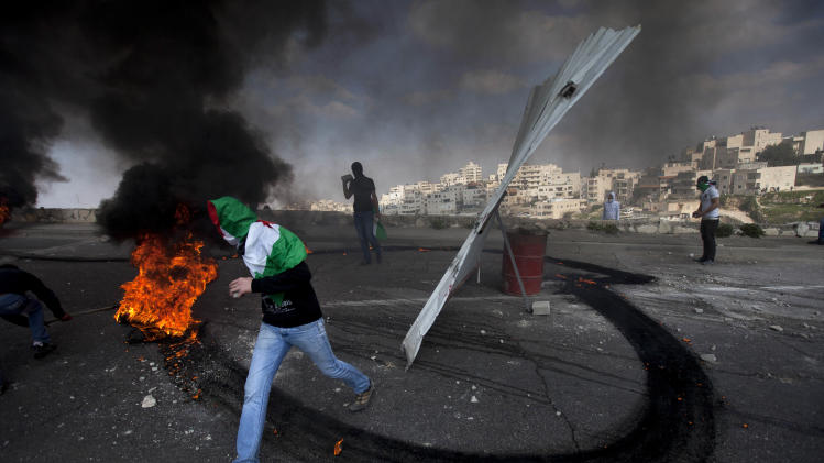 "Masked Palestinians clash with Israeli troops as they mark the ""Land Day"" in the east Jerusalem neighborhood of Issawiyeh, Friday, March 30, 2012. Israeli security forces in riot gear Friday confronted Palestinian demonstrators, anticipating possible clashes along Israel's frontiers on ""Land Day"". The ""Land Day"" rallies are an annual event marked by Israeli Arabs and Palestinians in the West Bank and Gaza who protest what they say are discriminatory Israeli land policie. (AP Photo/Oded Balilty)"