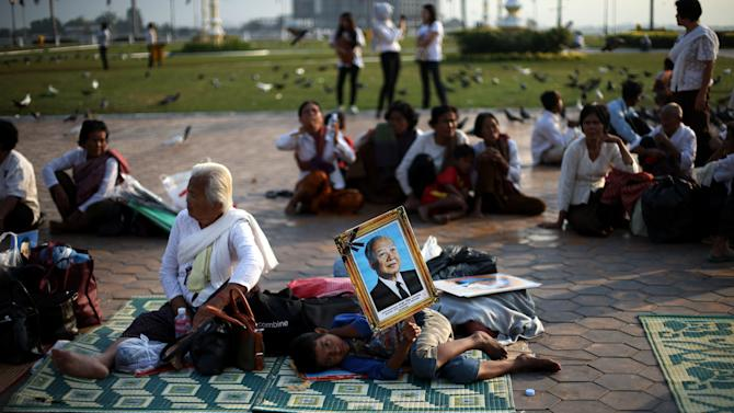 Mourners rest in a field in front of the Royal Palace where they body of the late former Cambodian King Norodom Sihanouk rests in Phnom Penh, Saturday, Feb. 2, 2013. Sihanouk's body had been lying in state at the Royal Palace after being flown from Beijing where he died Oct. 15 of a heart attack at the age of 89. The cremation, the climax of seven days of mourning, will take place Monday.(AP Photo/Wong Maye-E)
