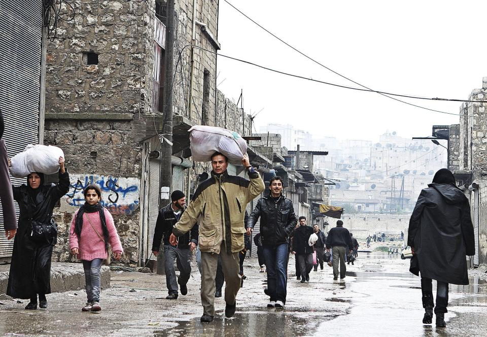In this Wednesday, Feb. 6, 2013 photo, Syrian people carry their belongings after they crossed the river which separates between Free Syrian Army fighters and government forces in the Bustan Al-Pasha neighborhood, north of Aleppo, Syria.(AP Photo/Abdullah al-Yassin)