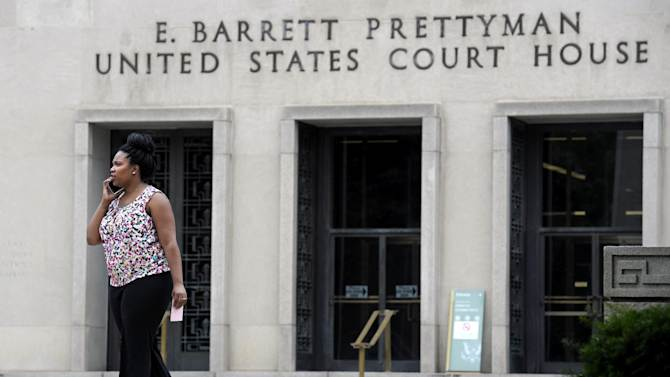 FILE - In this June 6, 2013, file photo, a woman talks on the phone outside the U.S. Courthouse in Washington, Thursday, June 6, 2013, where the secret Foreign Intelligence Surveillance Court resides. Stung by public unease about new details of spying by the National Security Agency, President Barack Obama selected a panel of advisers he described as independent experts to scrutinize the NSA's surveillance programs to be sure they weren't violating civil liberties and to restore Americans' trust. But with just weeks remaining before its first deadline to report back to the White House, the review panel has effectively been operating as an arm of the Office of the Director of National Intelligence, which oversees the NSA and all other U.S. spy efforts.(AP Photo/Cliff Owen, File)