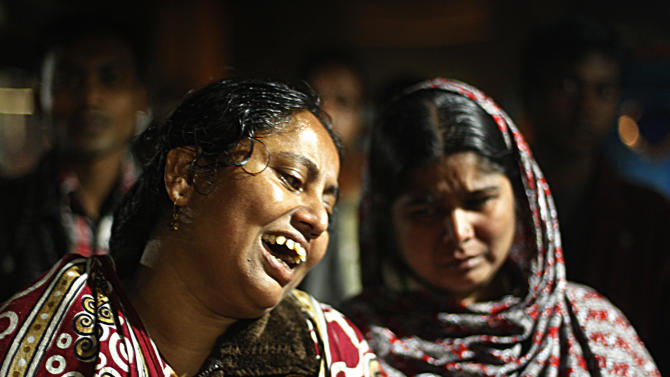 Bangladeshi women react at the scene of a fire at a garment factory in the Savar neighborhood in Dhaka, Bangladesh, late Saturday, Nov. 24, 2012. At least 112 people were killed in a fire that raced through the multi-story garment factory just outside of Bangladesh's capital, an official said Sunday. (AP Photo/Hasan Raza)