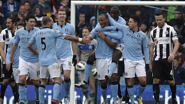 Manchester City's players celebrate with Vincent Kompany (4R) after he scored his side's third goal during their English Premier League soccer match against Newcastle United at The Etihad Stadium in Manchester, northern England, March 30, 2013 (Reuters)