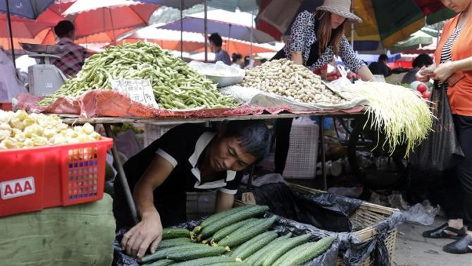 A vendor adjusts cucumbers for sale at a market in Beijing