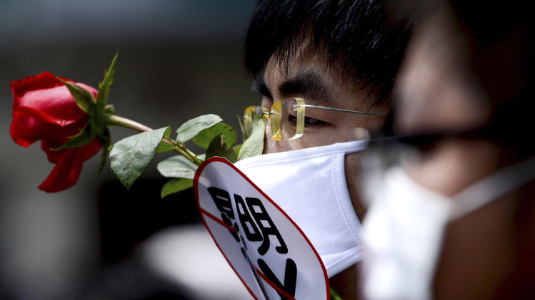 """A Chinese man wears a face mask with the word, saying """"No to Kunming PX,"""" paraxylene, as he and others take part in a protest against a planned refinery project in downtown Kunming in southwest China's Yunnan province Saturday, May 4, 2013. After word spread about an environmental protest that was planned for Saturday in the central Chinese city of Chengdu, drugstores and printing shops were ordered to report anyone making certain purchases. Microbloggers say government fliers urged people not to demonstrate, and schools were told to stay open to keep students on campus. Meanwhile, hundreds of people - many wearing mouth masks - gathered in Kunming to protest a planned refinery project in the area. The demonstrators demanded information transparency and that public health be safeguarded. (AP Photo) CHINA OUT"""
