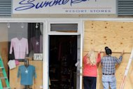 Bob Kaege and Marie Jadick board up the Summersalt store in preparation for Hurricane Sandy in Cape May, New Jersey. Across the eastern US, Americans made frantic preparations for a possible superstorm as Hurricane Sandy lumbered north after leaving 59 people dead in the Caribbean