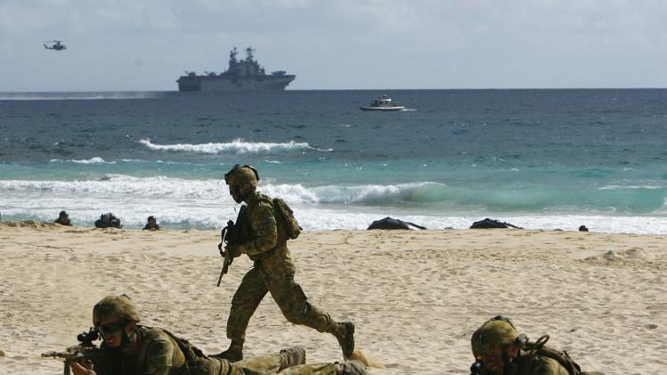 Australian Army soldiers from 5th Battalion, Royal Australian Regiment make their way up the beach after landing in amphibious assault vehicles from USS Peleliu in an assault exercise at Marine Corps Base Hawaii during RIMPAC in Kaneohe