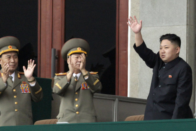 North Korean leader Kim Jong Un, right, waves as North Korean military officers clap during a mass meeting of North Korea's ruling party at a stadium in Pyongyang, North Korea on Saturday April 14, 2012. North Korea will mark the 100-year birth anniversary of the late leader Kim Il Sung on Sunday, April 15.