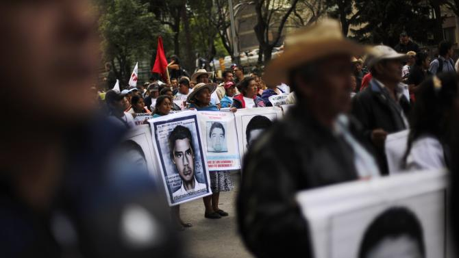 Relatives of the 43 missing students from Ayotzinapa Teacher Training hold portraits of the students during a march to demand justice for the students in Mexico City