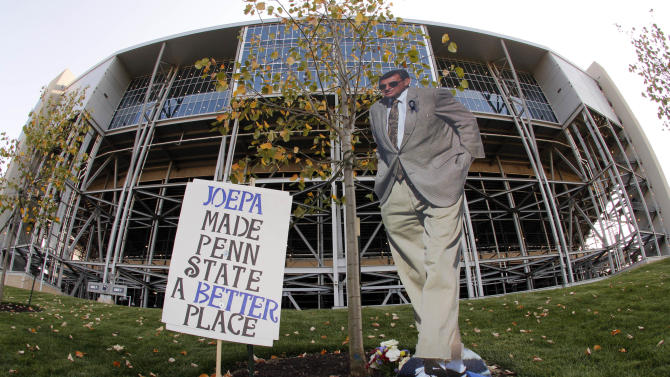 In this photo made with a fisheye lens a cardboard stand up of former Penn State head football coach Joe Paterno, stands near the site where a 9-foot bronze statue of Paterno once stood outside Beaver Stadium on Penn State's main campus in State College, Pa., Friday, Aug. 31, 2012. Penn State opens its football season at home Saturday against Ohio University. (AP Photo/Gene J. Puskar)
