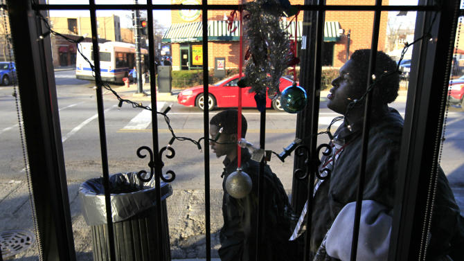 In this Monday, Dec. 3, 2012 photo, two boys walk past Christmas decorations in the barred window of a business along 79th Street in the Auburn-Gresham neighborhood on Chicago's South Side. The violence in 2012 has gripped a handful of neighborhoods, including Auburn-Greshman, where the police districtís 43 homicides (as of Dec. 21) ranked highest in the city. This one corridor on the city's South Side offers a window into the larger mayhem. (AP Photo/Charles Rex Arbogast)