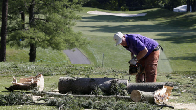 A worker chainsaws a tree that fell onto a tee box on the the 12th hole at Congressional Country Club in Bethesda, Md., Saturday, June 30, 2012, after a strong storm blew through overnight. The AT&T National golf tournament was postponed to allow workers to clear the course. (AP Photo/Patrick Semansky)