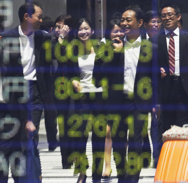 People are reflected on the electronic board of a securities firm in Tokyo, Monday, June 18, 2012. Asian stock markets climbed Monday after elections in Greece eased fears of global financial turmoil,